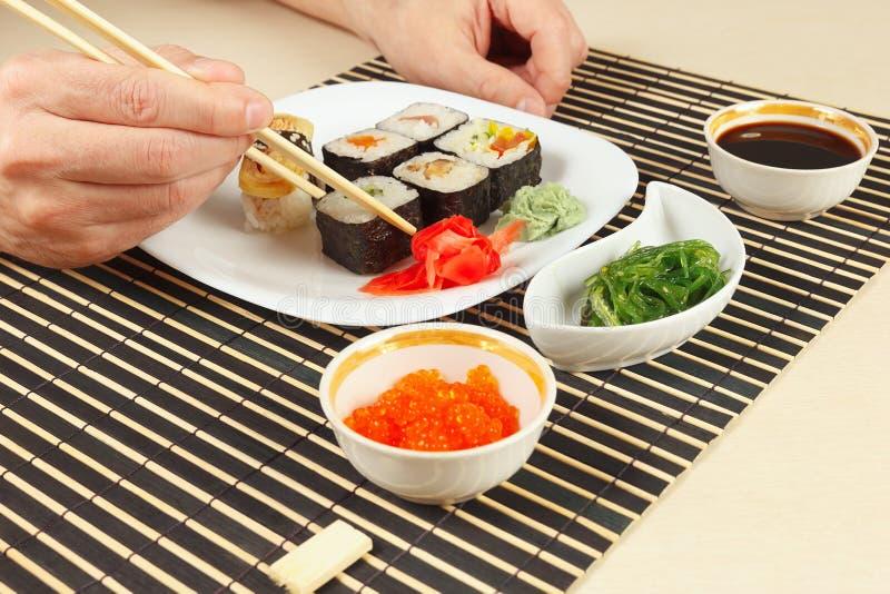 Händer som tar sushirulle med pinnar Sushiuppsättning, chukasallad, soya och laxkaviar på matt svart bambu arkivfoto