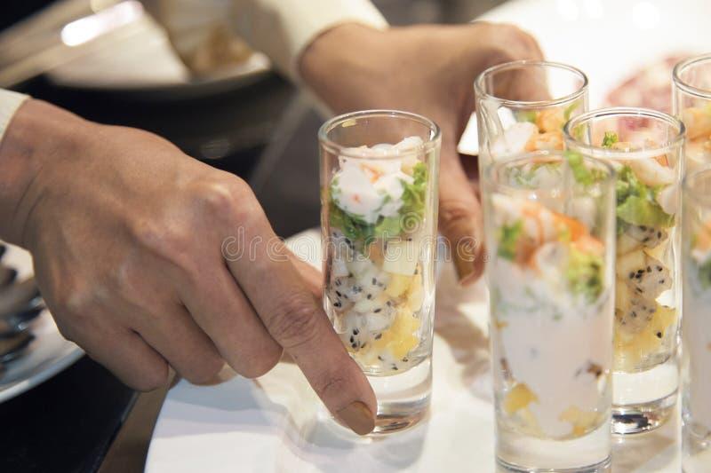 Händer som tjänar som coctailskott med frukter royaltyfri foto