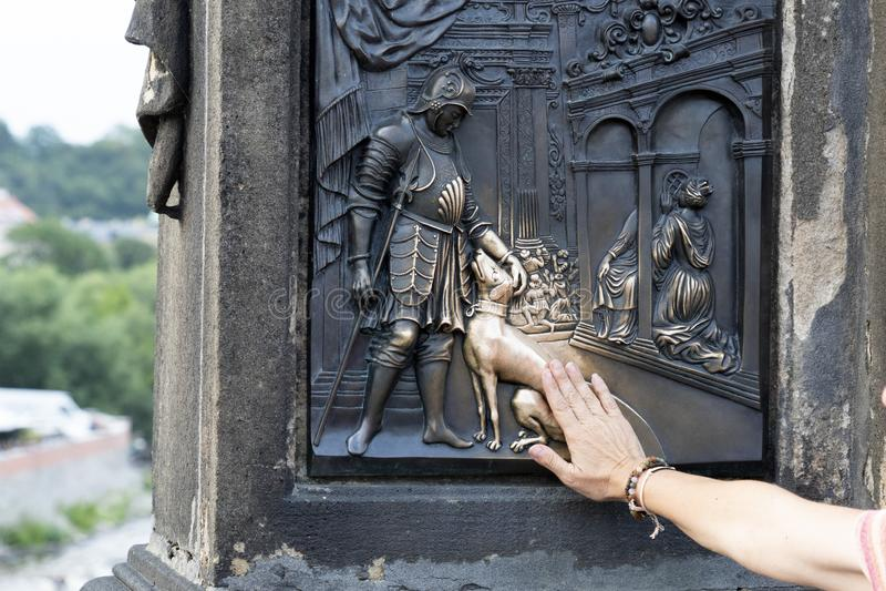 Händer som trycker på hundstatyn på den charles bron prague arkivfoton