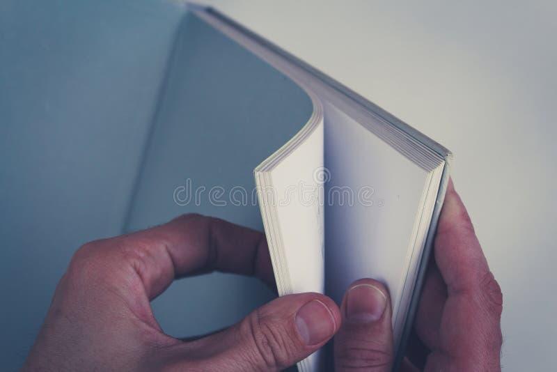 Händer som vänder sidor i tom bok med tomma sidor royaltyfri bild