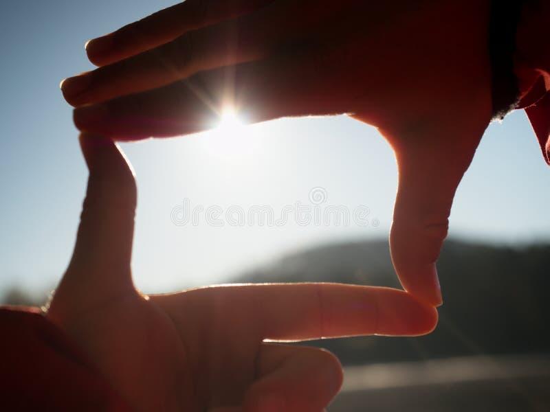 Händer sträcker in mot solen på sjönivå royaltyfri fotografi