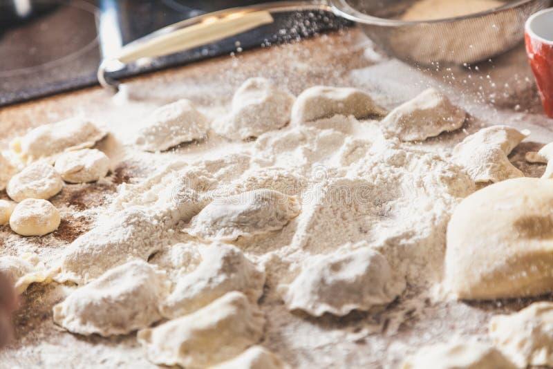 Händer strilar med rå klimpar för mjöl på tabellen royaltyfri bild