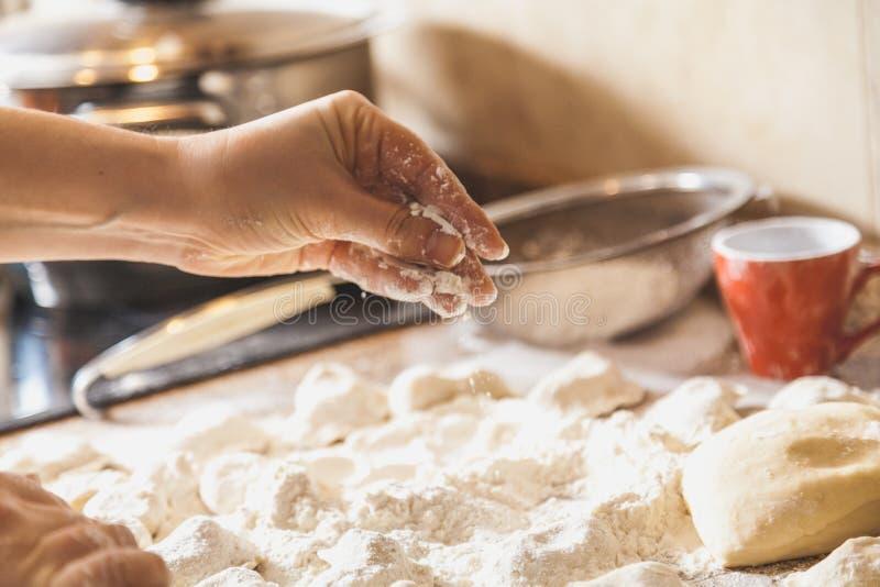 Händer strilar med rå klimpar för mjöl på tabellen arkivfoton