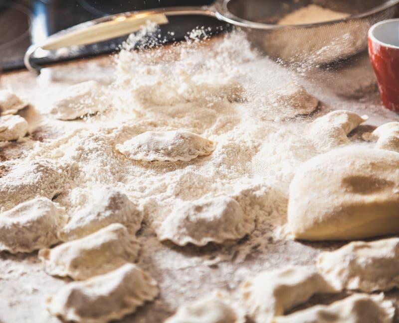 Händer strilar med rå klimpar för mjöl på tabellen royaltyfri fotografi