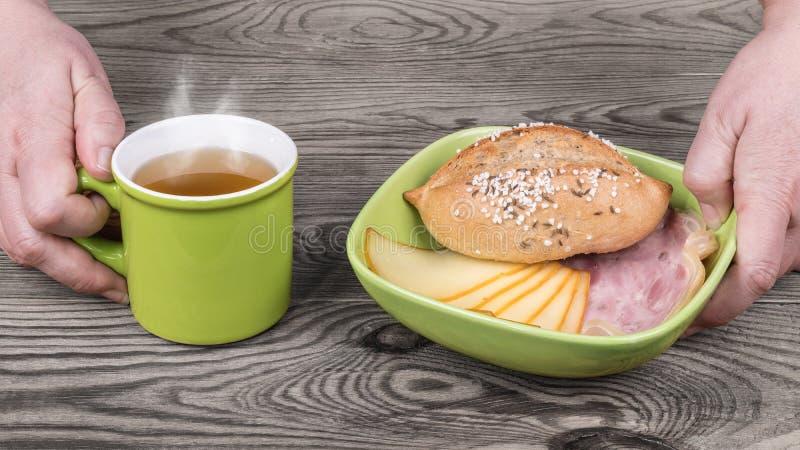 Händer tjänar som den hurtiga frukosten med varmt te arkivfoton
