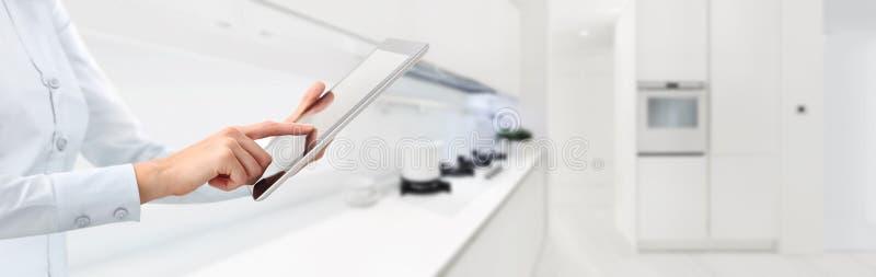 Händer trycker på den digitala minnestavlan på smart hem för kökbakgrund royaltyfri bild