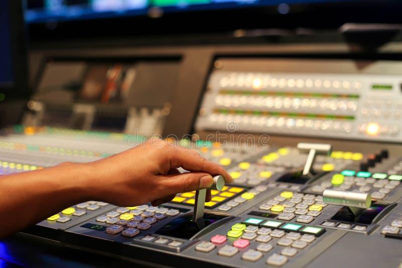 Händer upplöser på av Switcherknappar i studioTV-station, Audi arkivfoto