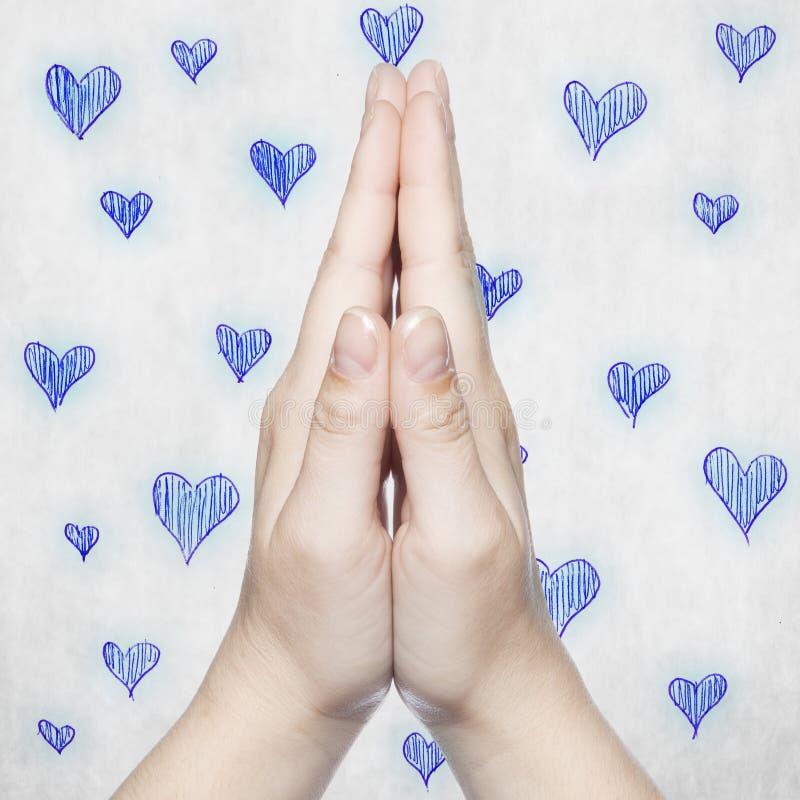 Händer vek i bön, då med blåa hjärtor arkivbilder