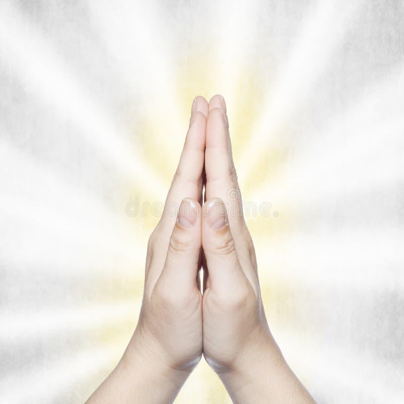 Händer vikta i bön med en ljusblixt royaltyfri foto