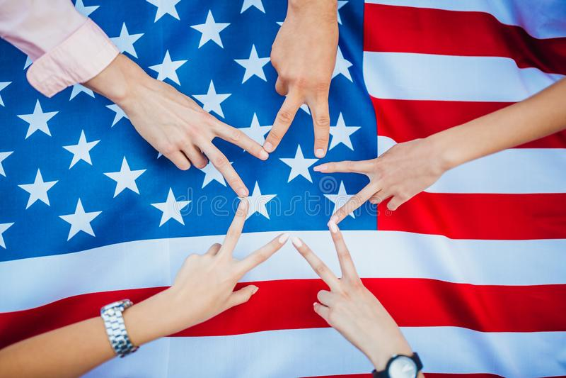 Händerna av amerikaner mot bakgrunden av USA-flaggan retro sj?lvst?ndighet f?r bakgrundsdaggrunge arkivfoton