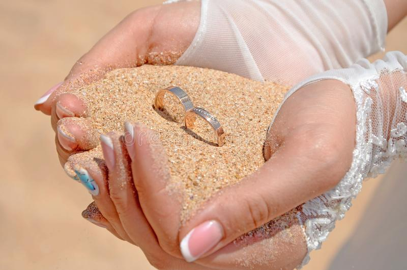Händerna av bruden i vita handskar rymmer en handfullsand och två guld- vigselringar royaltyfri bild