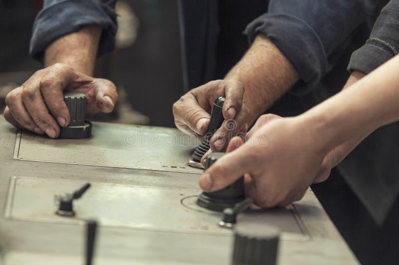 Händerna av de två funktionsdugliga strömbrytarespakarna och knopparna arkivfoto