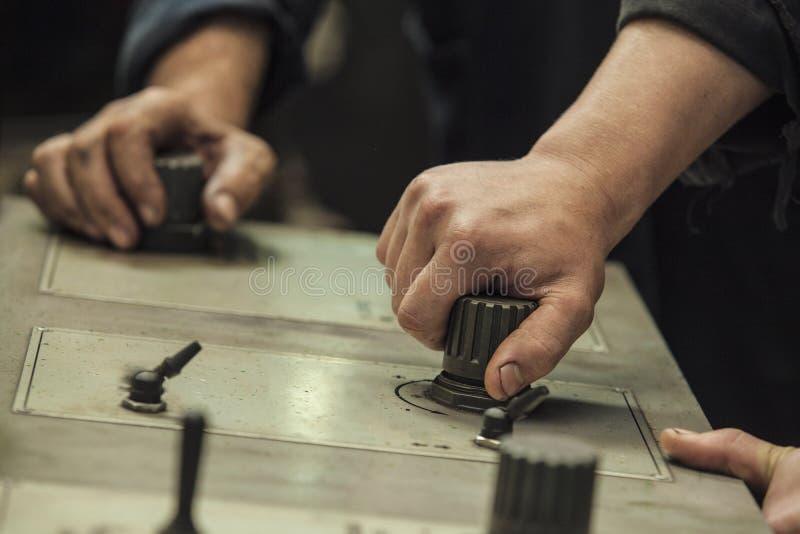 Händerna av de två funktionsdugliga strömbrytarespakarna och knopparna arkivfoton
