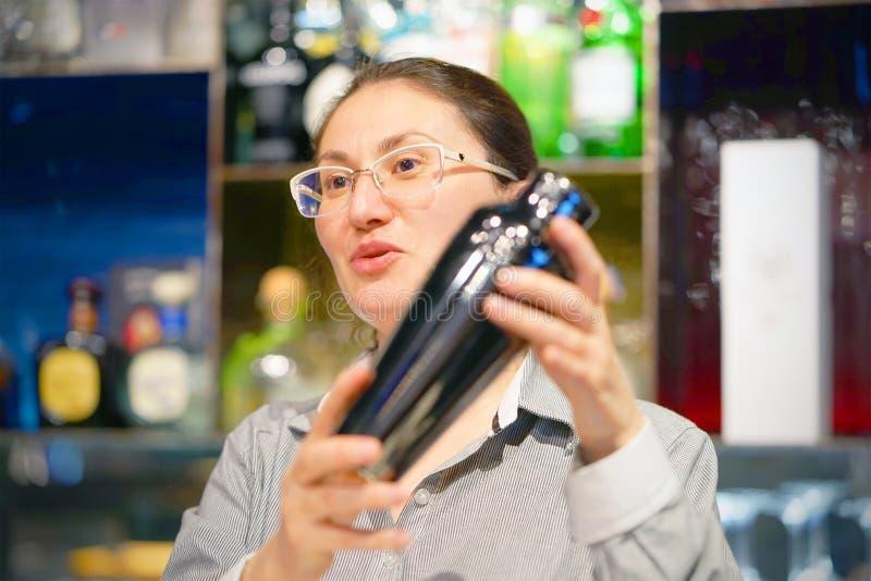 Händerna av en bartenderkvinna rymmer en yrkesmässig shaker arkivbild