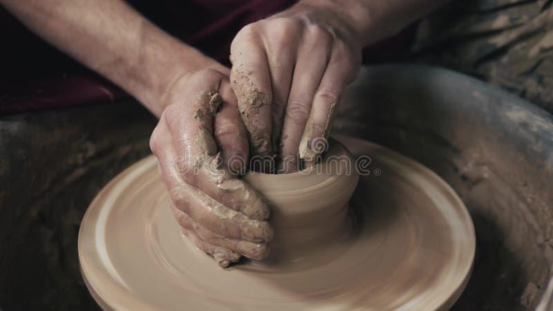 Händerna av en keramiker som skapar en jord- krus på cirkeln, närbild, händer på cirkel med lera arkivbild