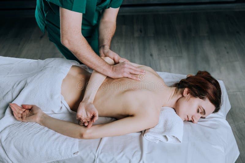Händerna av en manlig massör som gör massage av en ung kvinna Härlig avkopplad framsida av en ung kvinna 27 gamla år med brun hai arkivfoto