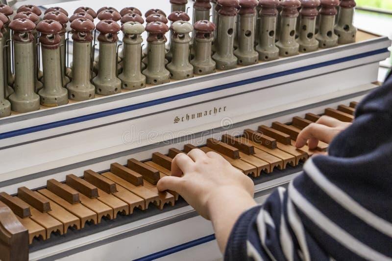 Händerna av en oidentifierad pojke som spelar en kunglig öppen dag på Organbuilding Schumacher i Eupen, Belgien, selektiv fokus royaltyfri fotografi