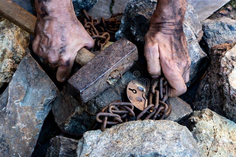 Händerna av en slav i ett försök att släppa Symbolet av slav- arbete H?nder i kedjor arkivbild