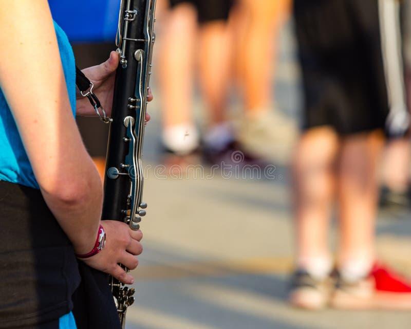 Händerna av en spelare för bas- klarinett royaltyfri fotografi