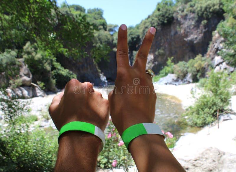 Händerna av ett par av den unga handelsresanden på klyftor för en flod parkerar royaltyfria foton