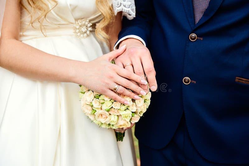 Händerna av nygifta personerna som bär deras vigselringar Brudgum- och guldcirklar för brud och royaltyfria foton