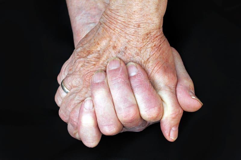 Händerna av två gamla kvinnor arkivfoto