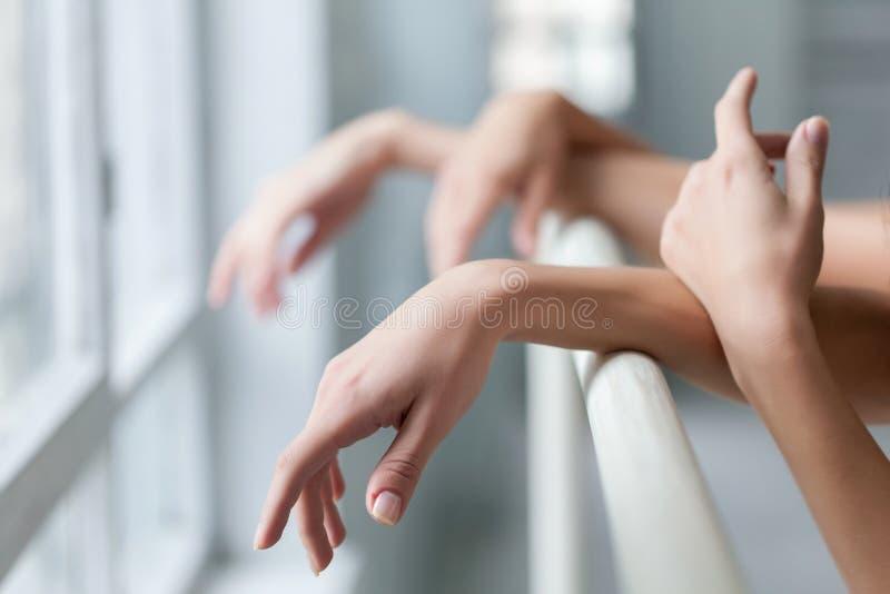 Händerna av två klassiska balettdansörer på barren royaltyfri bild