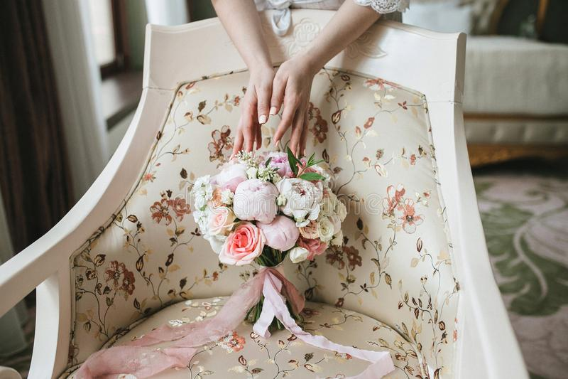 Händerna för brud` s trycker på en härlig bröllopbukett av rosa och vita pioner, som står på en beige stol för tappning royaltyfria bilder