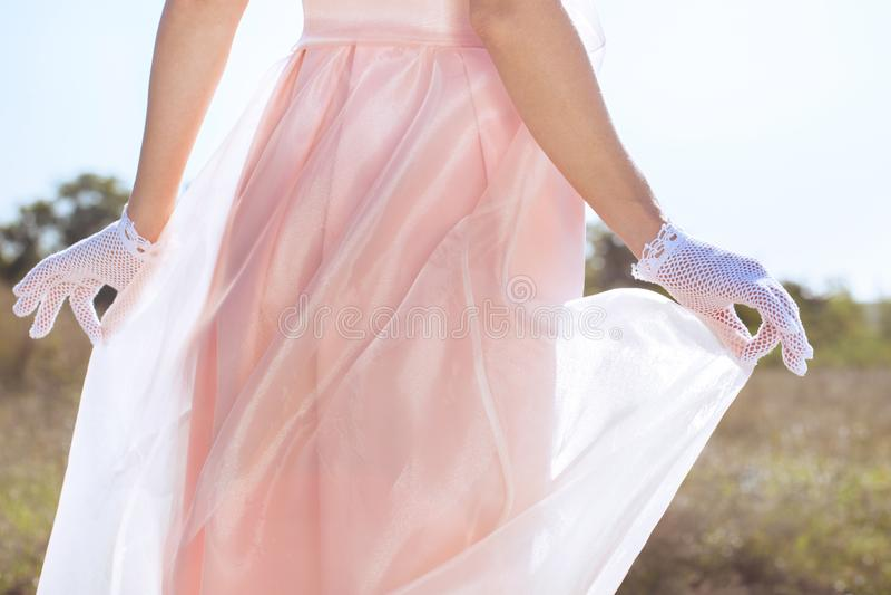 Händerna i vita handskar rymmer en klänning royaltyfria bilder