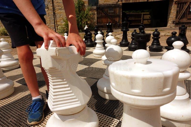 Händerna och foten av en pojke som flyttar riddarestycket på ett jätte- utomhus- schackbräde royaltyfri foto