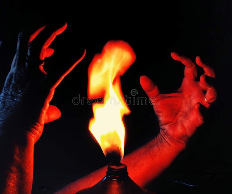 Händerna som försöker att trycka på branden royaltyfri bild