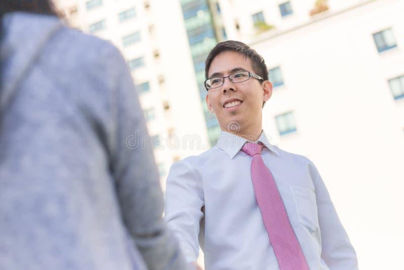 Händeschütteln des asiatischen Mannes und der Frauen des Geschäfts im Freien mit buildin lizenzfreie stockbilder