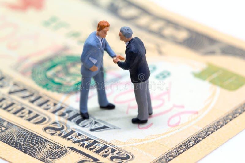 Händeschüttelngeschäftsmänner auf USA-Dollarbanknote Unternehmenseinträgliches geschäft stockfotos