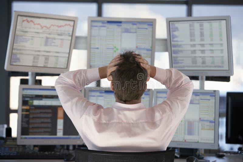 Händler auf Lager Watching Computer Screens mit den Händen auf Kopf lizenzfreies stockfoto