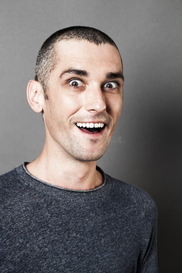 Hänförd man som skrattar för att uttrycka hans glädje och häpnad fotografering för bildbyråer