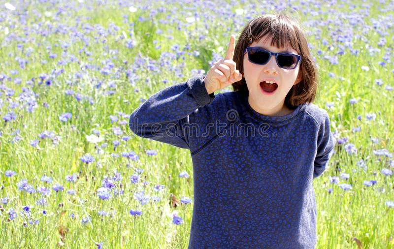 Hänfört uttrycksfullt barn med solglasögon över den soliga blåklintängen som är utomhus- royaltyfria bilder