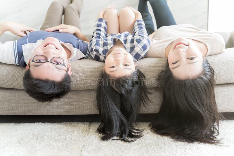 Hänga för familj för stående som lyckligt asiatiskt är uppochnervänt på soffan i vardagsrum royaltyfri foto