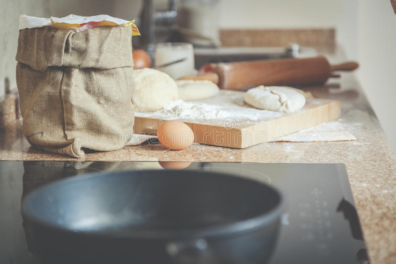 Hänga löst mjöl, ägget, bräde med den grillade lilla pastejen på marmorcountertop arkivfoto