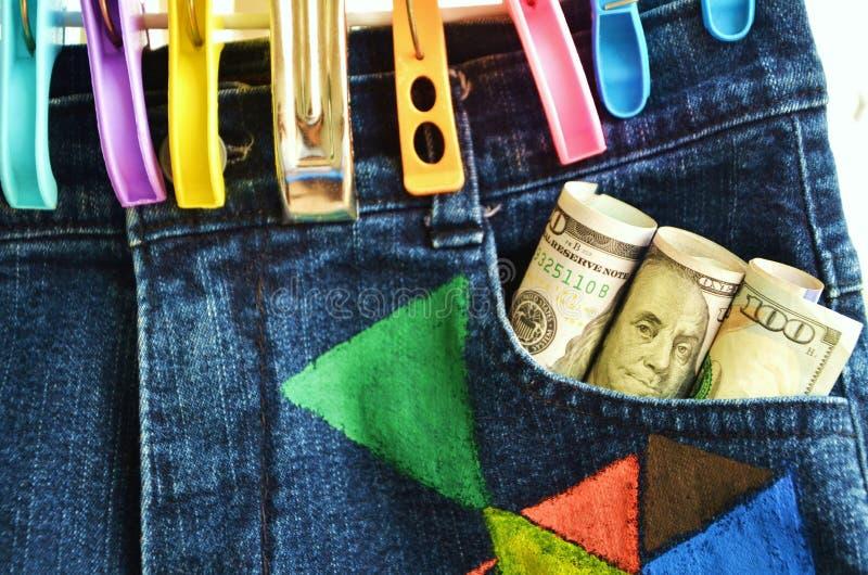Hänga och klädnypor för jeans byx- med dollarbanker arkivfoto