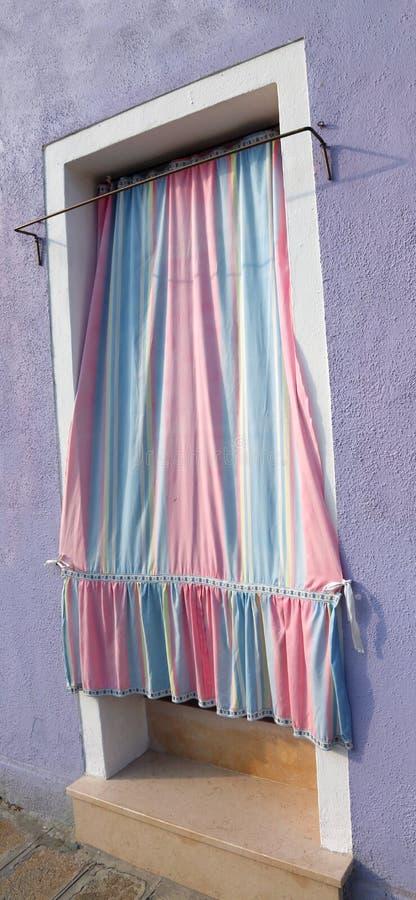 Hänga upp gardiner på ingången av ett hus i Burano arkivfoto
