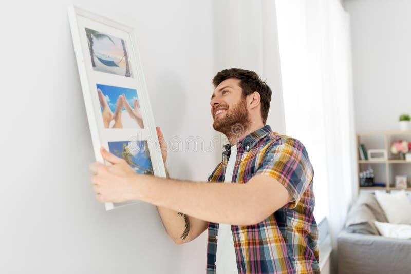 Hängande bild för man i ram till väggen hemma arkivbilder