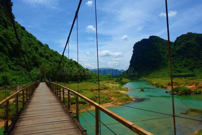 Hängande bro med en sikt av den gröna vattenströmmen i Phong Nha, Ke-smällnationalpark, Vietnam arkivbilder