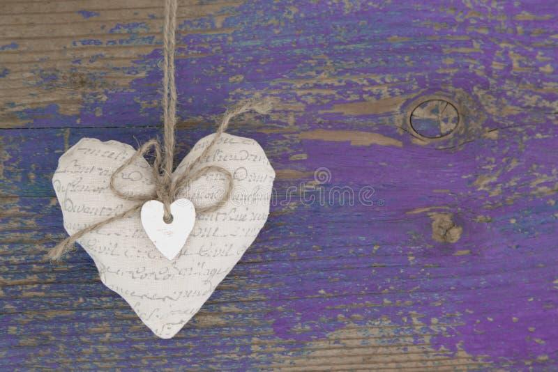 Hängande hjärta och purpurfärgad träbakgrund i landsstil. royaltyfri bild