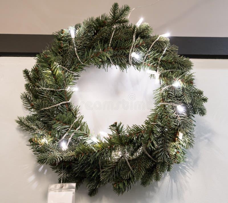 Hängande jul rundar kransen som dekoreras med spiralen lett ljus c arkivfoton