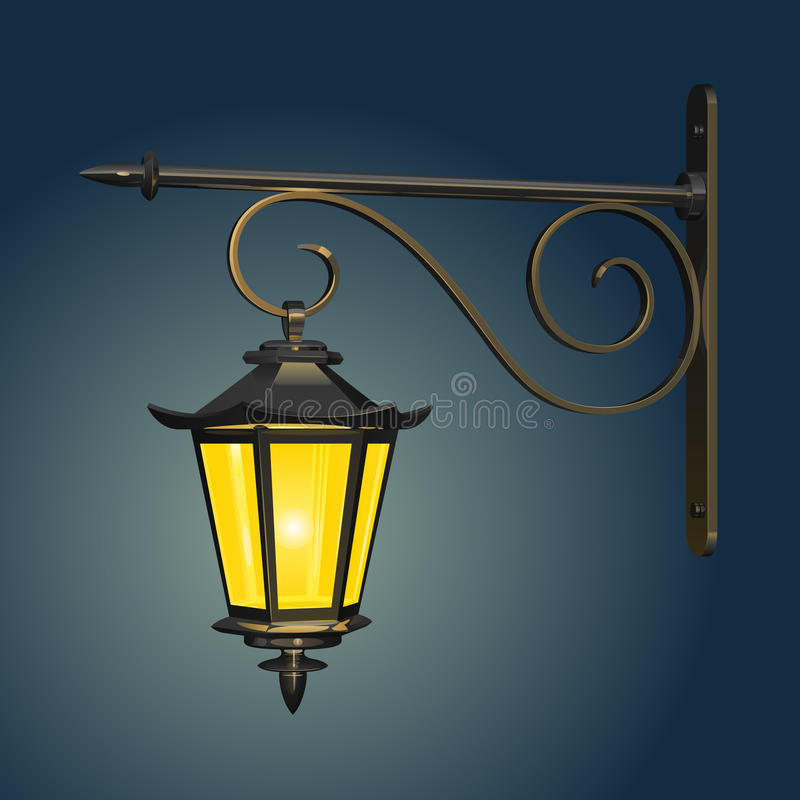 Hängande lampa för tappninggata som glöder med gult ljus mot aftonhimlen, med en järn- väggmontering royaltyfri illustrationer