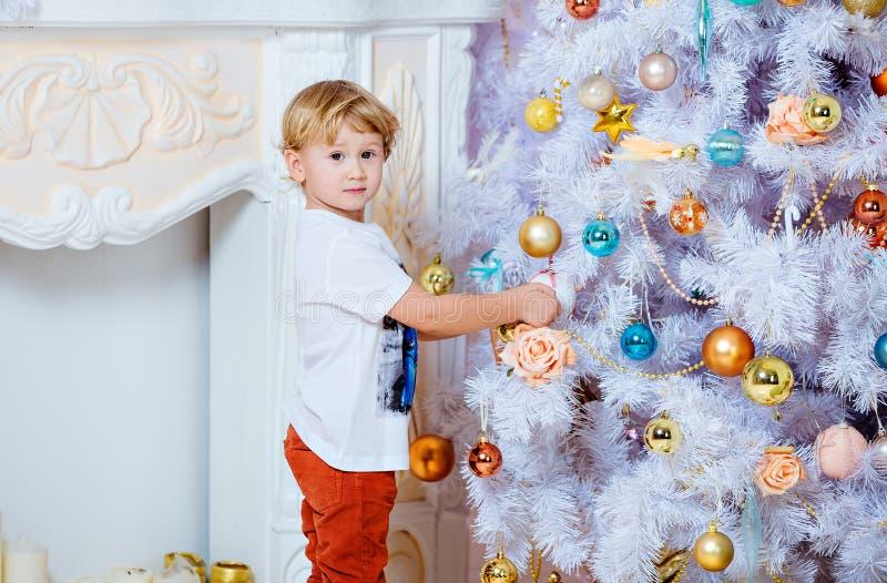 Hängande leksaker för liten mycket gullig blond pojke på en vit julgran fotografering för bildbyråer