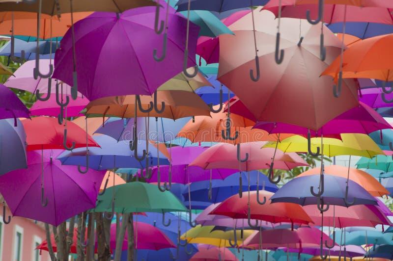 Hängande mång- kulöra paraplyer över himmel arkivfoton