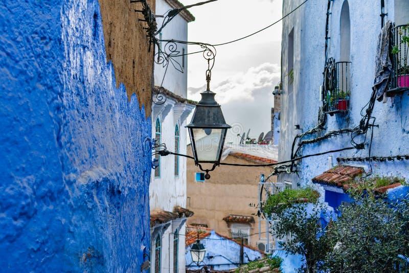 Hängande Streetlight i en smal gata i Chefchaouen Marocko med blåa byggnader arkivbild