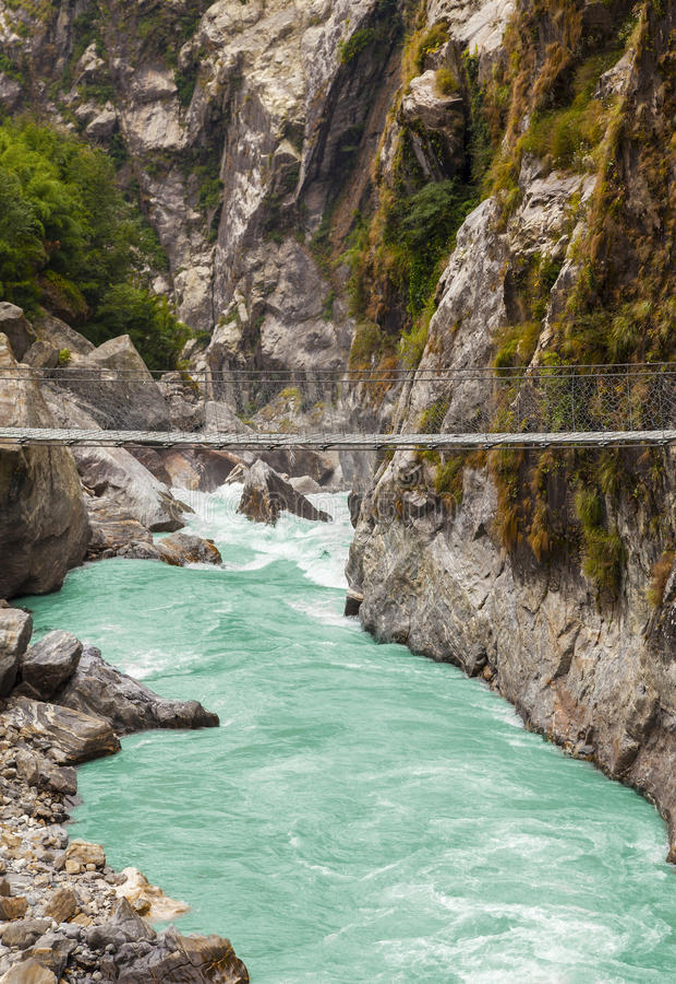 Hängande upphängningbro i Himalaya berg, Nepal arkivfoton
