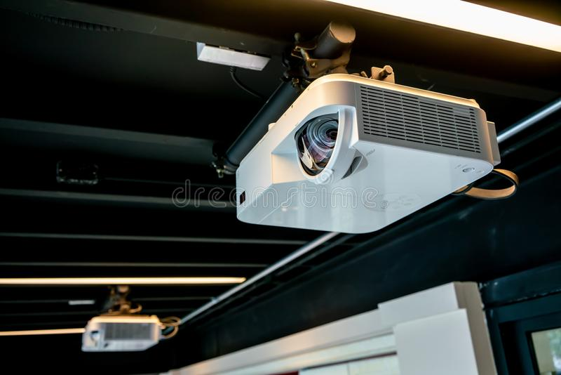 Hängande vit projektor för svart tak mot svart bakgrund arkivfoto